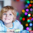 Little blond child playing with cars and toys at home — Stock Photo #61783497