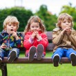 Two little boys and one girl eating chocolate — Stock Photo #61784625