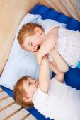 Little sibling boys having fun in bed at home — Stock Photo