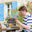 Young man having breakfast outside in summer with various jams,  — Stock Photo #62354111