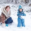 Little preschool boy and his mother playing with first snow in p — Stock Photo #62354947