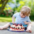 Little boy celebrating his birthday in home's garden with big ca — Stock Photo #62355089