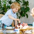 Little boy celebrating his birthday in home's garden with big ca — Stock Photo #62355175