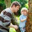 Cute little kid boy enjoying climbing on tree with father, outdo — Stock Photo #62355267