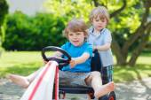 Two funny little boys having fun with race car outdoors — Foto Stock