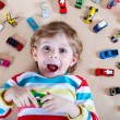 Adorable little boy playing with lots of toy cars indoor — Stock Photo #62668591