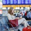 Woman at international airport, reading ebook and drinking coffe — Stock Photo #62669257