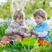 Two little boy friends in Easter bunny ears during egg hunt — Foto Stock