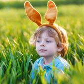 Cute little child with Easter bunny ears playing in green grass  — Stock Photo