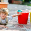 Little toddler boy having fun with splashing water in summer gar — Stock Photo #63789295