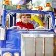 Funny little kid boy riding on a merry-go-round carousel — Stock Photo #63789957