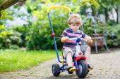 Active blond kid boy driving tricycle or bicycle in domestic gar — Stok fotoğraf