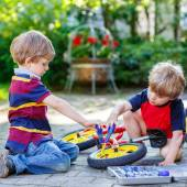 Father teaching two little kid boys to repair chain on bikes — Stockfoto