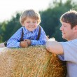 Young father and his little son having fun on yellow hay field i — Stock Photo #63791365