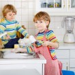 Two funny little boy friends washing dishes in domestic kitchen — Stock Photo #63791567