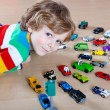 Little blond kid boy playing with lots of toy cars indoor — Stock Photo #63791675