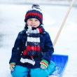 Cute little funny boy in colorful winter clothes having fun with — Stock Photo #63791969
