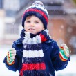 Cute little funny boy in colorful winter clothes having fun with — Stock Photo #63791977