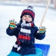 Cute little funny boy in colorful winter clothes having fun with — Stock Photo #63791999