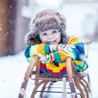 Cute little funny boy in colorful winter clothes having fun with — Stock Photo #63792033