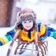 Cute little funny boy in colorful winter clothes having fun with — Stock Photo #63792055
