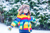 Cute little funny boy in colorful winter clothes having fun with — Stock Photo
