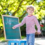Little boy at blackboard learning to write — Stock Photo #64898797