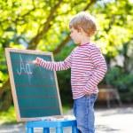 Little boy at blackboard learning to write — Stock Photo #64898801