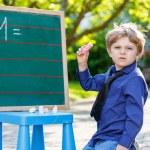 Little boy at blackboard learning to write — Stock Photo #64898817