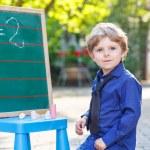 Little boy at blackboard learning to write — Stock Photo #64898849