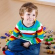 Funny little boy playing with lots of toy cars indoor — Stock Photo #64899937