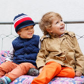 Two happy boys on hollywood swing in spring garden — Stockfoto
