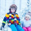 Portrait of two kids: boy and girl in winter hat in snow forest — Stock Photo #64900313