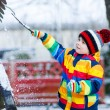 Little  boy in colorful winter clothes playing with snowman, out — Stock Photo #64900451