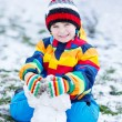Little  boy in colorful winter clothes playing with snowman, out — Stock Photo #64900511