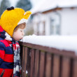 Little kid boy in colorful clothes happy about snow, outdoors — Stock Photo #64900589