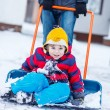 Funny kid boy having fun with riding on snow shovel, outdoors — Stock Photo #64900805
