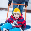Funny kid boy having fun with riding on snow shovel, outdoors — Stock Photo #64900817