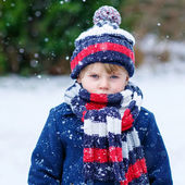Sad kid boy in colorful winter clothes having fun with snow, out — Stock Photo