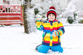 Little boy playing with snow in winter, outdoors. — Stock Photo