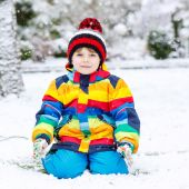 Funny preschool boy in colorful clothes happy about snow, outdoo — Stock Photo