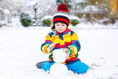 Funny preschool boy in colorful clothes making a snowman — Stock Photo