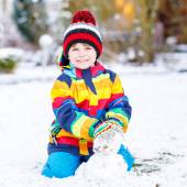 Beautiful kid boy in colorful clothes making a snowman — Stock Photo