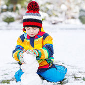 Lovely little boy in colorful clothes making a snowman — Stock Photo