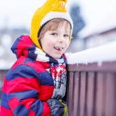 Little kid boy eating and tasting snow, outdoors on cold day — Stock Photo