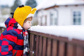 Little kid boy in colorful clothes happy about snow, outdoors — Stock Photo