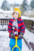 Funny little boy in colorful clothes happy about snow, outdoors — Stock Photo