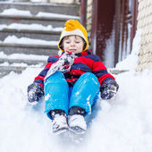 Happy child in colorful clothes having fun with riding on snow,  — Stock Photo