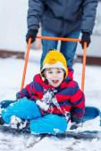 Funny kid boy having fun with riding on snow shovel, outdoors — Stock Photo