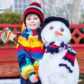 Funny kid boy in colorful clothes making a snowman — Stock Photo